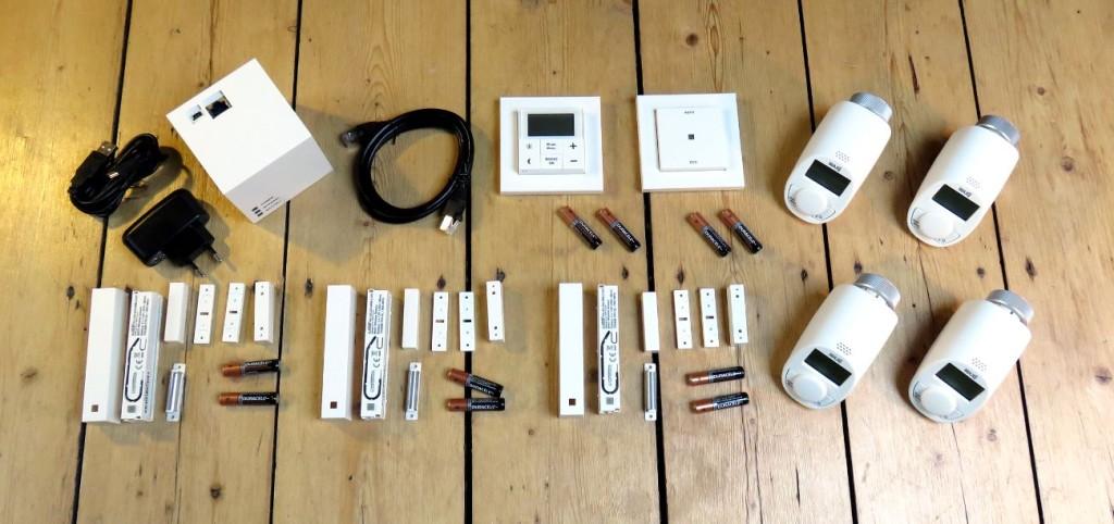 Es ist der ausgepackte Inhalt des MAX! Heizungssteuerung Starterpaketes, also alle vorgestellten Komponenten plus ein weiteres MAX! Heizkörperthermostat Basic zu sehen.