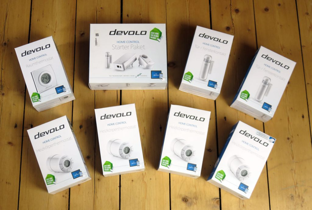 Auf diesem Bild sind die verpackten Komponenten des Tests zu sehen: Devolo Home Control Starter Paket, Devolo Home Control Heizkörperthermostate, Devolo Home Control, Raumthermostat und Devolo Home Control Tür- und Fensterkontakte
